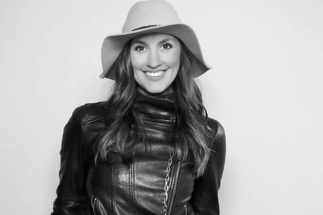 A black and white photo booth image of a woman in a hat