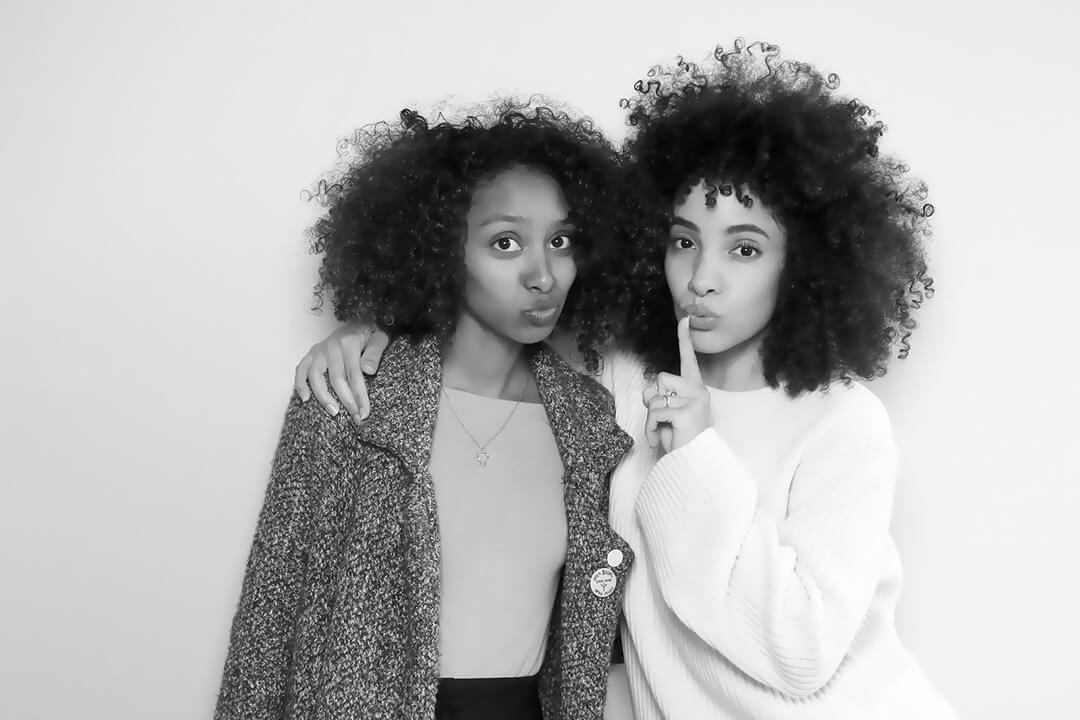Two friends with natural hair pose in a black and white photo booth
