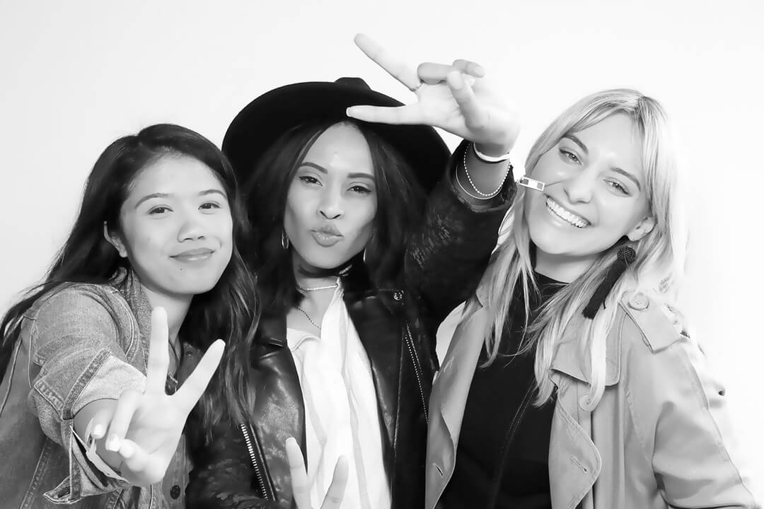 Three friends pose in a black and white photo with a beauty filter applied