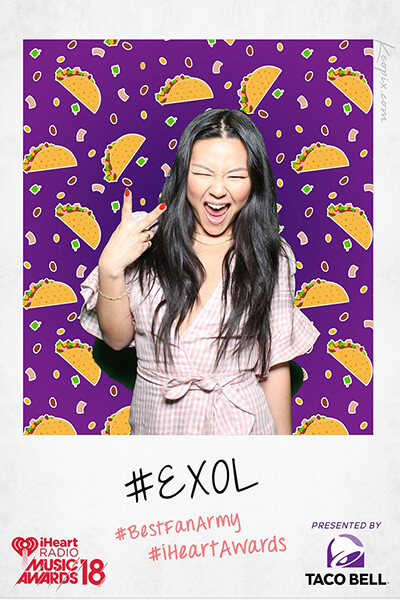 Green Screen image of a woman holding up the peace sign in front of a wall of tacos for the Taco Bell sponsored Photo-op