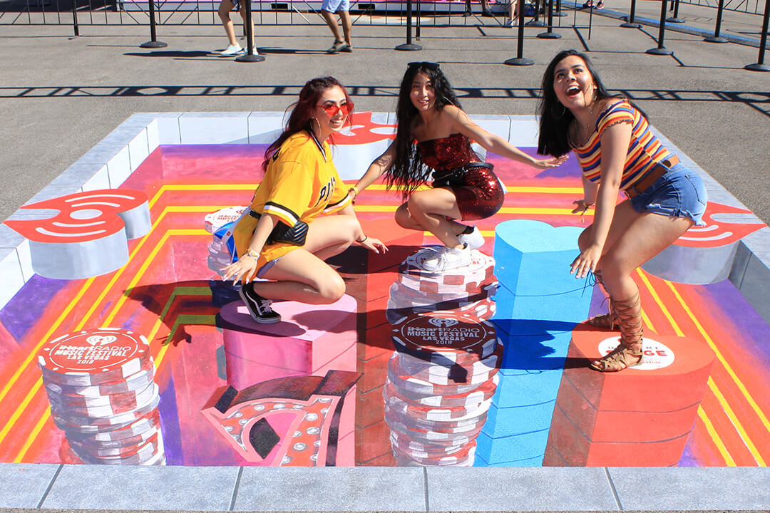 3 Friends pose together on the 3D chalk drawing at iHeartRadio Music Festival