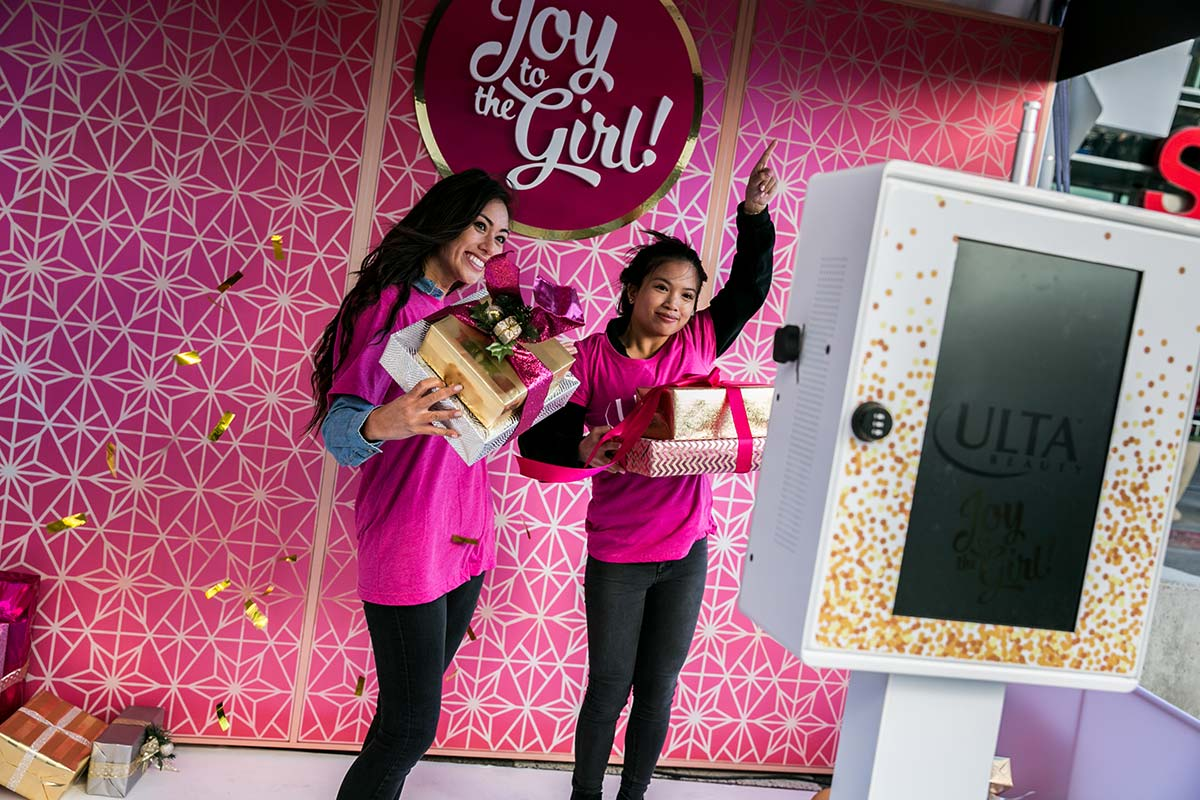 Two friends pose for the Ulta Beauty photo activation while holding Christmas presents and gold confetti floats in the air