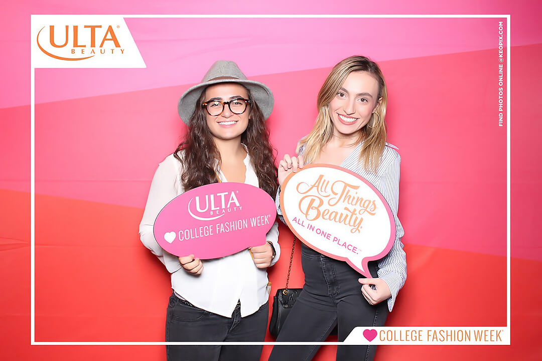 Two Women pose in the Ulta Beauty Photo Booth in front of a custom pink, orange and red backdrop at College Fashion Week