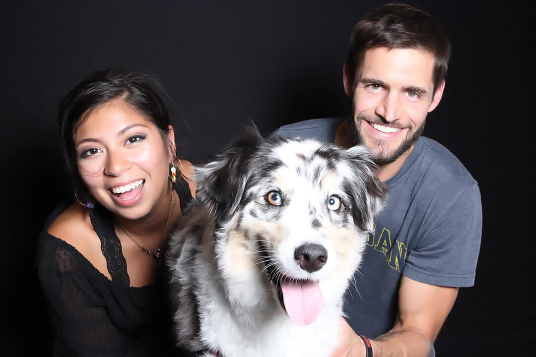 a couple poses with their black and white spotted dog
