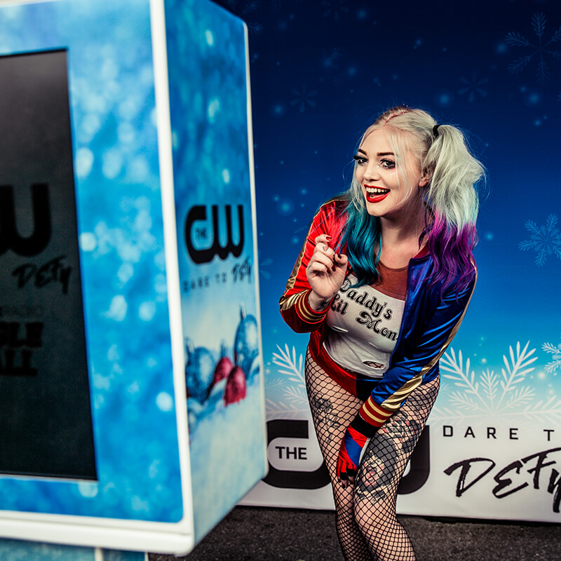 A woman poses in the photo booth at the Jingle Ball