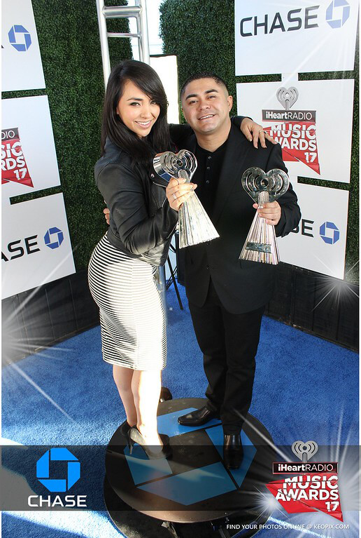 A couple poses with iHeartRadio Silver Trophies on the 360 Orbit Cam platform at the Chase sponsored Photo-op