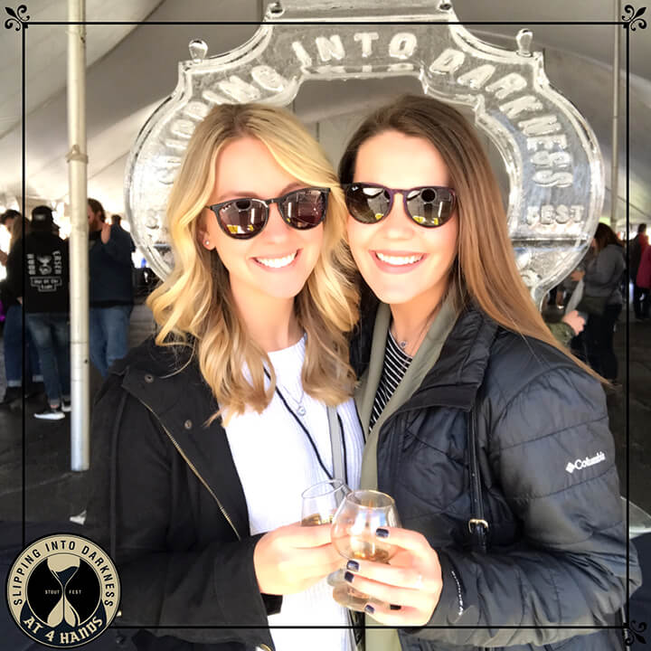 Two friends pose with beer glasses in front of an ice sculpture at a beer fest in St. Louis
