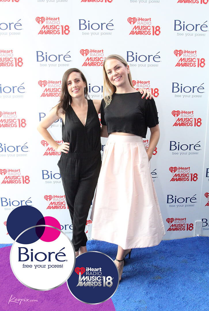 Two friends pose in front o the Biore step and repeat