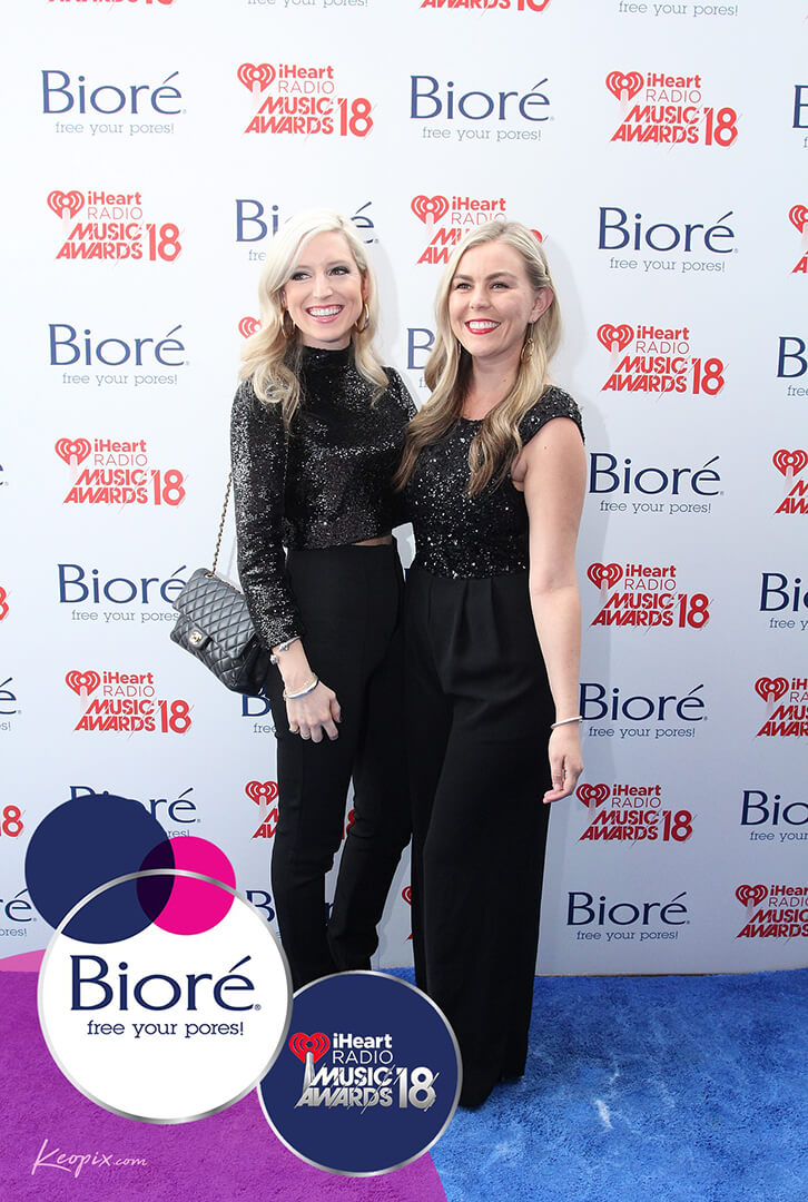Two women pose in front of a step and repeat backdrop