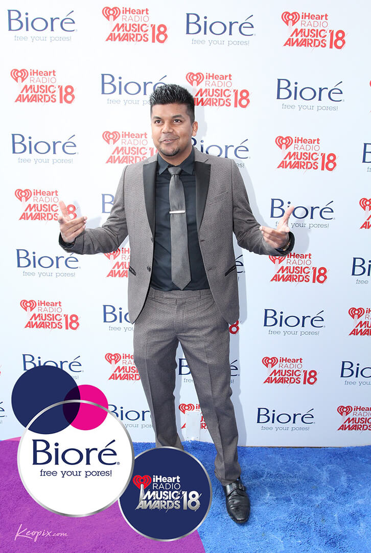Man in gray and black suit on the blue and purple carpet at the iHeartRadio Music Awards