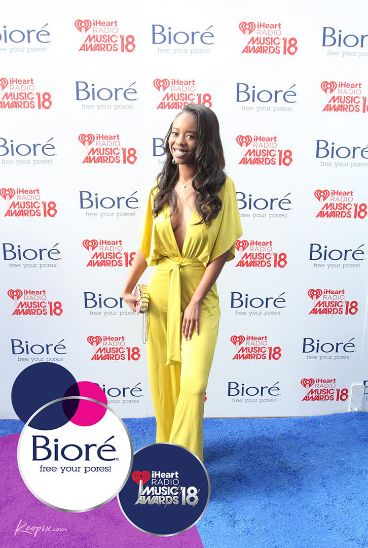 A woman in a yellow jumpsuit on the Biore carpet at the arrival to the 2018 iHeartRadio Music Awards