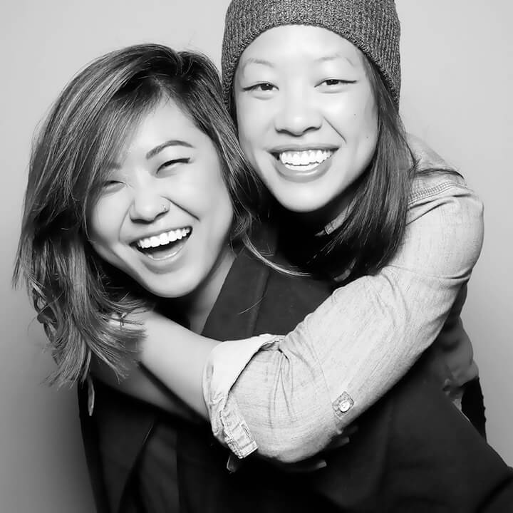 Image of two friends posing in a black & white photo booth with Glam filter applied.
