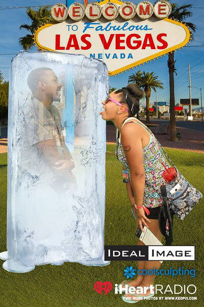 Green Screen photo of a woman licking an ice block with a man inside in front of the Las Vegas sign.