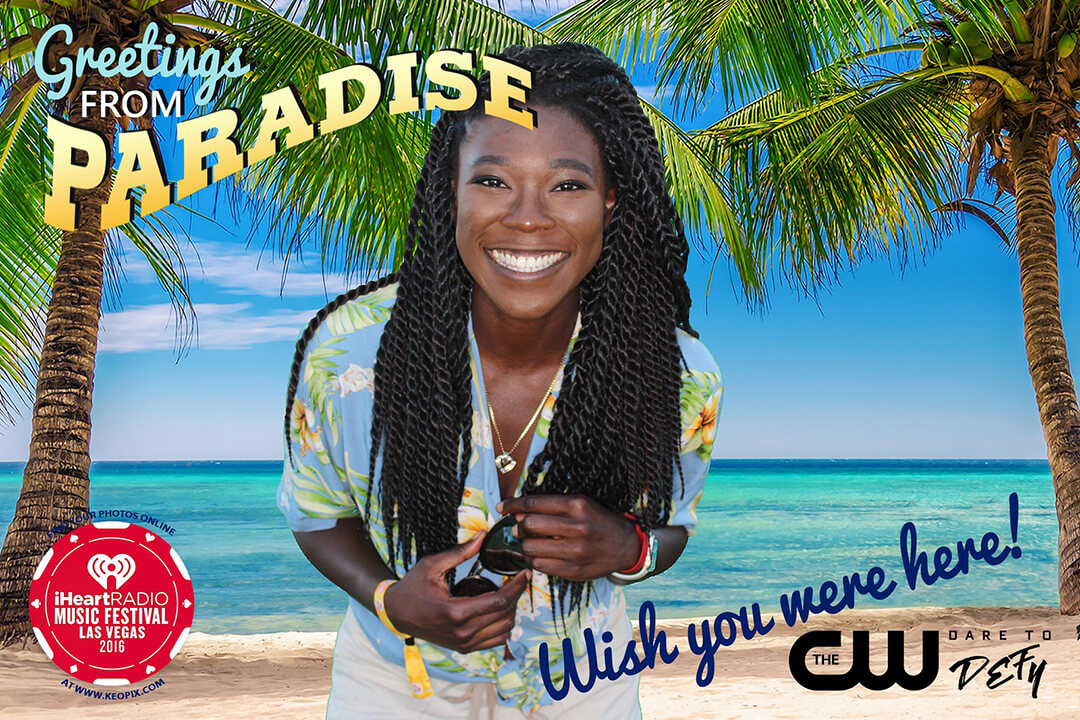 a woman poses in front of a green screen backdrop to produce a photo of her standing in front of a tropical beach