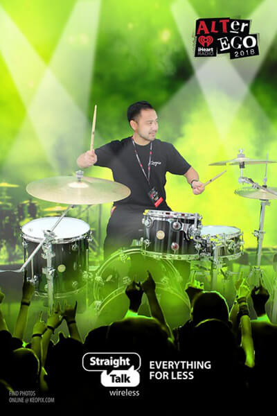 A man plays the drums in a front of a green screen to produce an image with green spotlights and smoke in the background